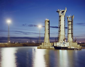 Sunset blue skies with lights reflecting on the water at Graythorp powerstation.