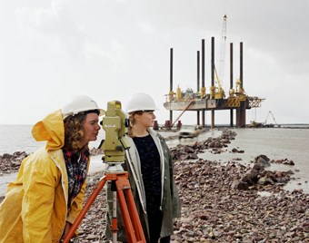 Two female Laing employees use a theodolite in front of the 'Jay Robertson' barge in the River Severn.