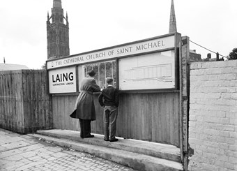 A man and boy looking through a viewing window at the construction site for Coventry Cathedral, with the Laing logo displayed on the left side, an elevation drawing of the cathedral displayed on the right side and a sign overhead displaying the cathedral name.