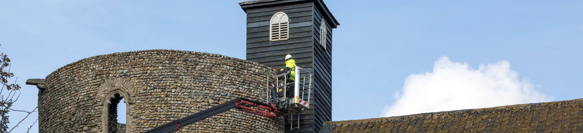 A man in high-vis jacket and hard hat works on the tower wall from a cherry picker.