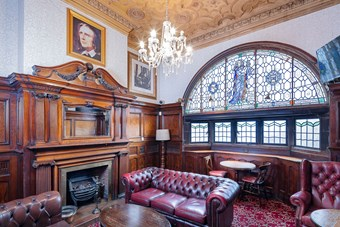 Ornate hardwood fire surround and furniture in a snug within a Victorian pub.