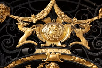Detail of a crest on an ornate decorative ironwork gate, painted black and gold,