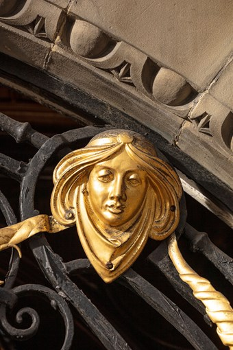 Detail of a female face on a decorative ironwork gate.