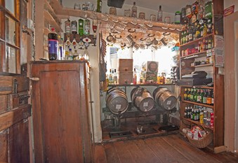 Detail of a servery in a pub with barrels, mugs, optics and shelves of bottles.