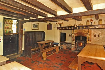 Cosy interior of a public house with panelled walls, ceiling beams and lit wood burning stove.