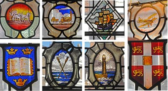 Stained glass window detailing from a public house including crests and depictions of heraldic crests and modes of transport.