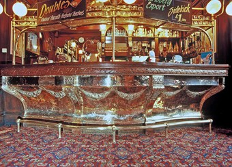A view of an elaborate copper bar counter at a public house.