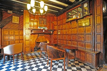 A view of a public bar area in a historic public house; features include wood wall panelling, a fireplace and section of exposed timber frame  with herringbone tile infilling.