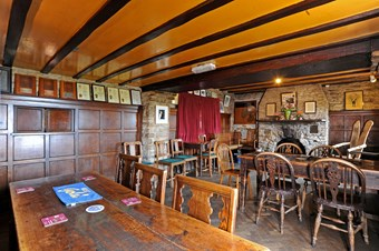 A large room in a historic pub; features include wooden panelling, exposed stonework and fireplace.
