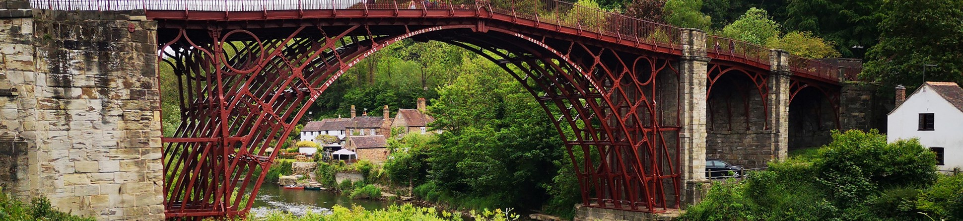 Cold-blast iron bridge spanning a river with thin iron parapet railings along the top.