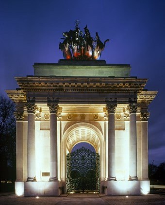a floodlit arch with the night sky and trees behind it. There is a metal gate in the centre of the arch