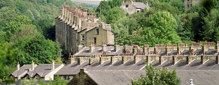 Photo of rooftops and chimneys of West Yorkshire terraced housing, nested within trees. The houses are sitting withing a small valley.