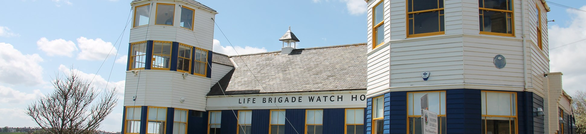 Photo of the outside of the Life Brigade Watch House - a white wooden building with blue and yellow painted windows.