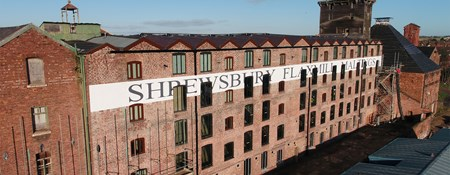 Red brick five-storey mill building with Shrewsbury Flaxmill Maltings sign written along it.