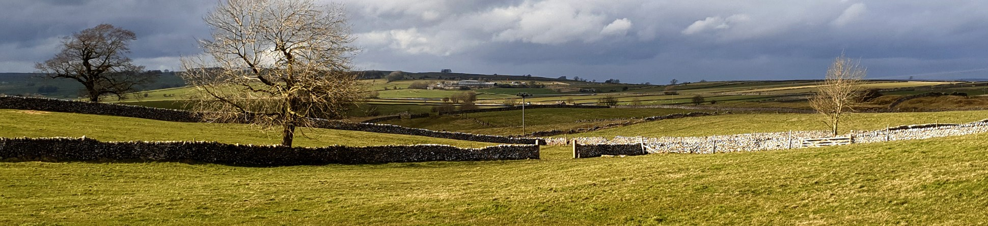 Magpie Mine, a scheduled monument near Bakewell, showing rolling fields and drystone walls.