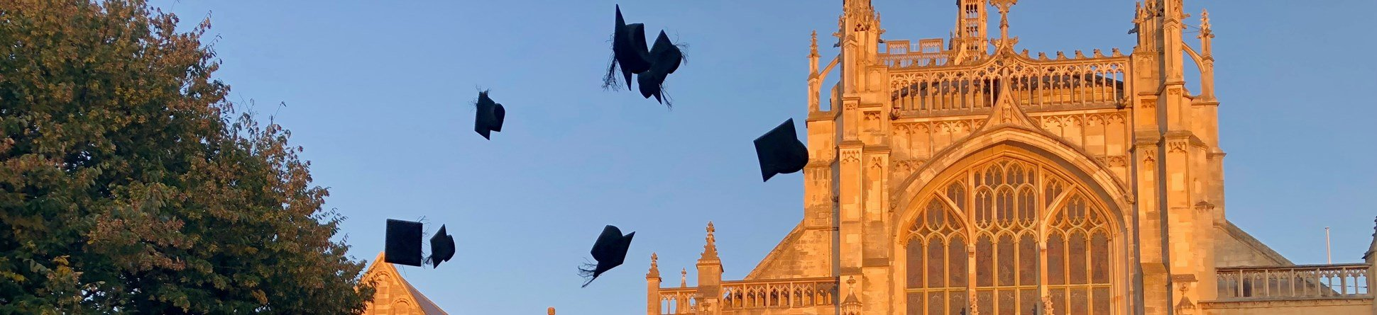 A group wearing graduation gowns throw their mortar boards in the air to celebrate. Behind them, light from the setting sun turns Gloucester Cathedral orange against a blue sky.