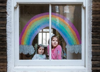 Two young girls sit beneath a rainbow painted on their front window
