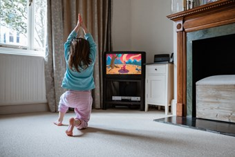 A young girl follows a children's yoga video in the living room