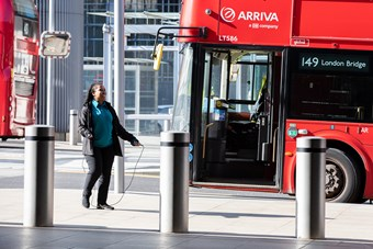 A bus driver strikes a jovial stance while exercising on her break, while working during lockdown in London.