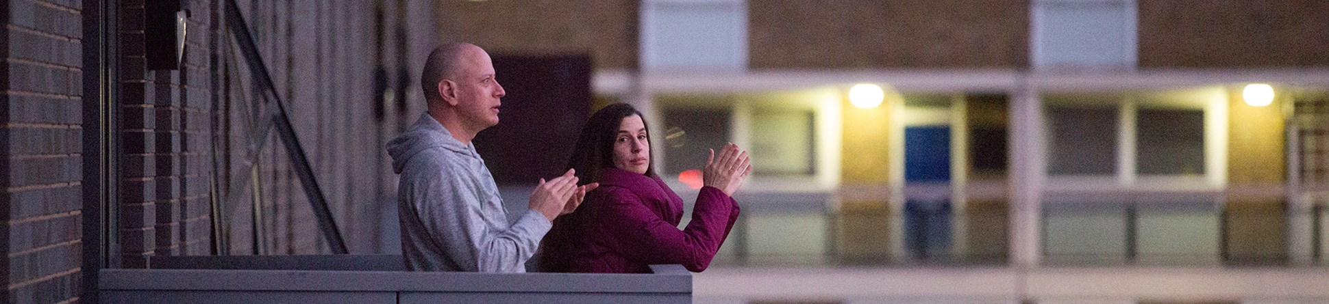 Man and woman standing on the balcony of a block of flats clapping their hands