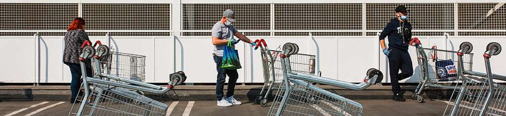 Three people standing 2 metres apart with supermarket trollies