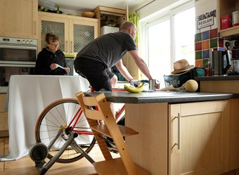 A man rides an indoor bike in his kitchen beside a woman holding a measuring tape above an ironing board.