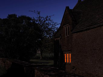 Orange light shines through a window at twilight. The home is made of Cotswold stone.