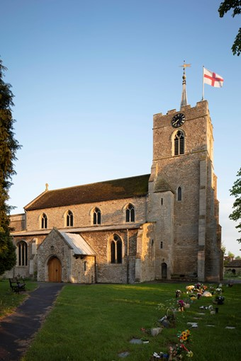 A church flies a St George flag. Fresh flowers have been laid on graves. The afternoon sun streams onto the roof.
