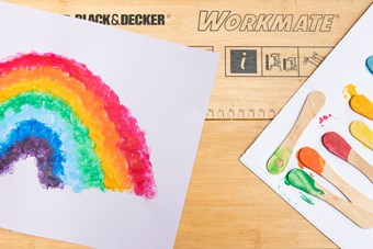 On the left hand side, a splotchy rainbow on a piece of white paper sits on top of a Black and Decker workboard. On the right hand side, a row of lolly sticks sit on an olod white envelope, with one end dipped in paint, each one representing a colour in the rainbow.