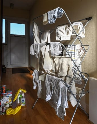 Baby clothes dry on a plastic clothes horse beside disinfectant products in a modern hallway.