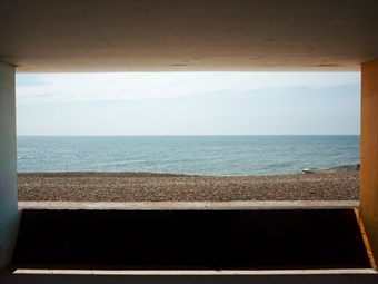 A view out to sea on a pebbly beach is framed by four concrete walls of a promenade.