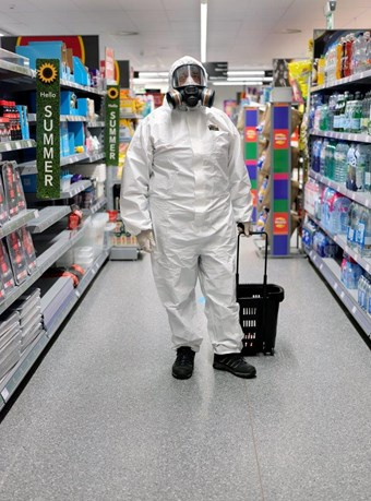 A man in full HAZ mask and suit carries a wheelie basket down a supermarket aisle.