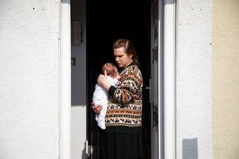 A woman stands at an open front door holding a newborn baby. She wears a brown fair-isle cardigan. The baby is in a white romper.