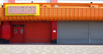 A large store front with corrugated orange facade and red shutters is closed. The shop is called 'sunspot; these words are signposted in pink and yellow. It is a warm sunny day.