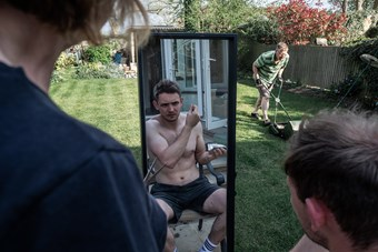 A topless young man, sat in a back garden, inspects his newly cut hairstyle in a long mirror. In front of him, a middle aged man mows the lawn and a woman beside him holds a pair of scissors.