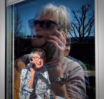 A woman has a conversation with her elderly mother via mobile phone. They can see each other through a sunny window.