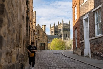 A woman in sunglasses and a face mask rummages inside a brown handbag whilst walking down an otherwise empty street in Durham. There are church towers in the background and a cobbled lane in the foreground.