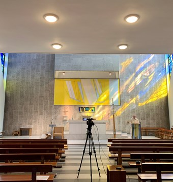 A priest gives a sermon to a video camera in an empty church. Light streams in from a yellow stained glass window.