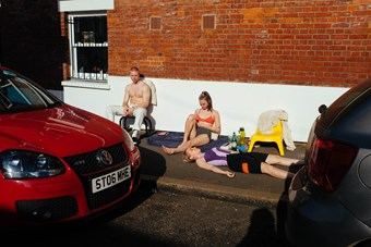 A young man and two young women lounge on a hot London pavement on a summer's day