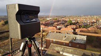 An image showing a 3D scanner with houses in the background