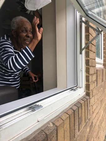 A 92 year old Ghanaian woman waving out her window.