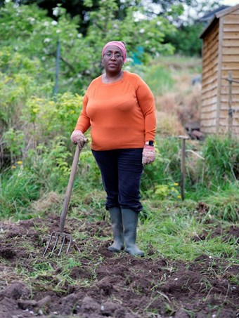 A woman posing with a gardening fork in an allotment.