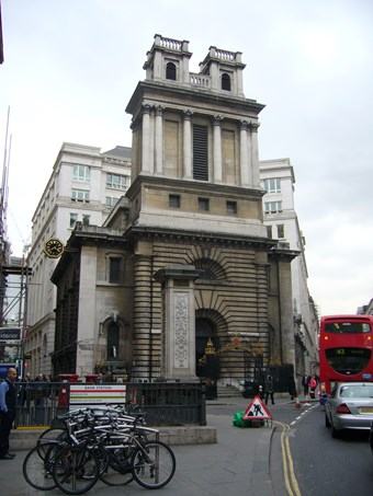 Imposing Baroque church of unusual design, on the corner of a busy London street. A red bus to right. The entrance bay is framed by plain columns, with deep rustication. Above, the broad rectangular tower has tall columns, and two square turrets.
