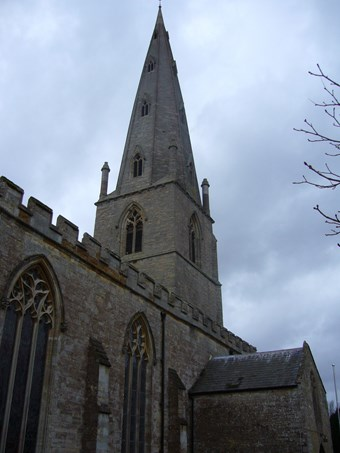 The west end of a church with a tall 14th-century pointed broach spire. The aisle wall in the foreground has pointed Gothic windows with tracery, and battlements. A stormy sky.