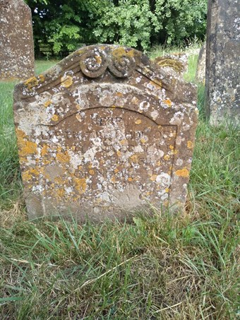 Headstone with scrolled detail to the top, the brown stone mottled with lichen. The indistinct inscription begins 'Here lieth the body of Myrtilla negro slave' and ends 'baptised October 20th, buried January 6th 1705'.