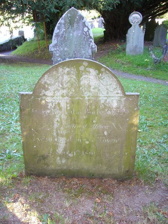 Modestly-sized headstone in a grassy churchyard; behind are other graves. An arched, shouldered, top, filled with foliate carving. The inscription is in a mixture of Roman and italic scripts; the date 'Sept 9th 1801' can just be made out.