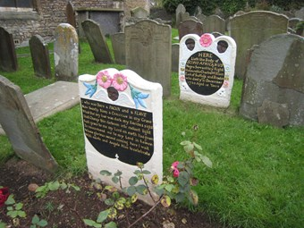 Headstone and footstone, with shaped tops. The freshly painted memorial stands out amongst unpainted stones. Carving includes winged Black cherubs, and flowers. The headstone carries the details of the subject's life; the footstone carries a verse.