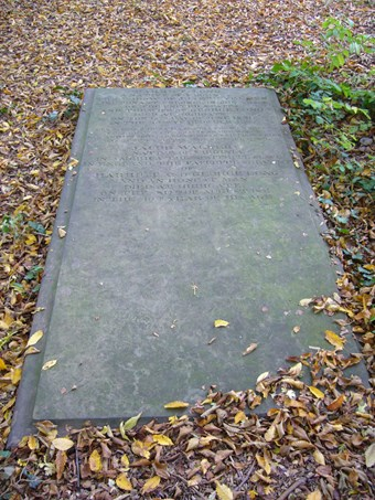 Large flat grey stone with moulded edge, seen from the bottom end, surrounded by autumn leaves. The inscriptions are at the top end of the stone, first the one for Harriet Long, then the one for Jacob Walker, who is described as 'an honest man'.