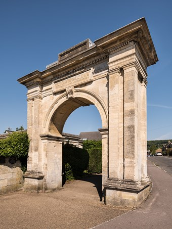 Freestanding stone archway. Arch flanked by coupled Doric pilasters, with cornice above. Between arch and cornice is a rectangular plaque, the inscription beginning Erected to commemorate the abolition of slavery. Behind, 20th-century housing.