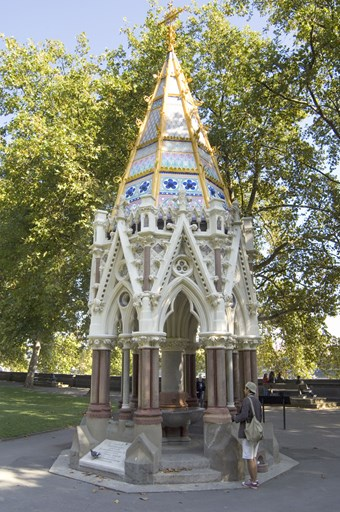 Elaborate Victorian Gothic pavilion, octagonal with a spire roof. Below, a stone arcade with pointed trefoil arches on red granite shafts. Above, the roof covered with bright enamelled decoration – pink, white, blue, green and yellow.